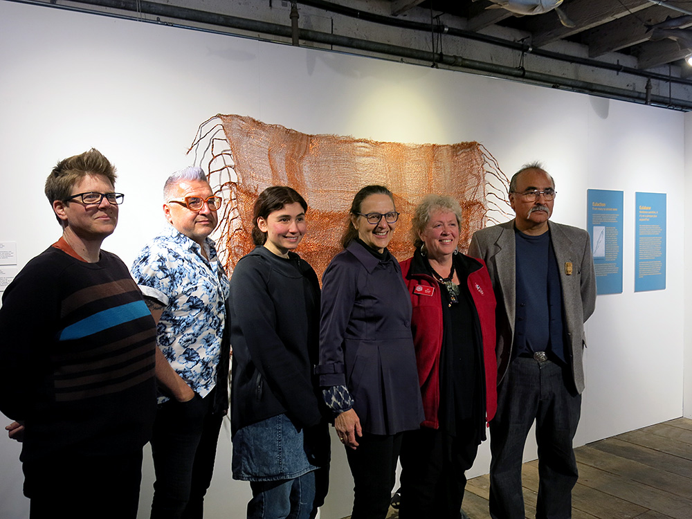Participating artists Kenna Fair, Richard Heikkilä-Sawan, Soledad Munoz, Ruth Beer, Kit Grauer & Lyle Wilson pose in front of Ruth Beer and Soledad Munoz copper weaving called 'Net Worth' 2015.